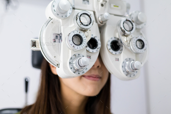 Woman doing eyesight measurement with optical phoropter - Stock Photo - Images