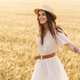 Photo of beautiful happy woman smiling and walking on wheat field - PhotoDune Item for Sale