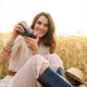 Photo of woman using retro camera while sitting on wheat field - PhotoDune Item for Sale
