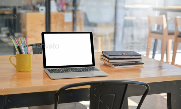 A laptop and notebook with stationery are placed on the table in the comfortable workspace. - Stock Photo - Images