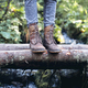 closeup of woman hiking boots on wooden bridge in the woods - PhotoDune Item for Sale
