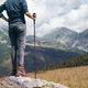 rear view of woman with hiking stick looking at the mountains - PhotoDune Item for Sale