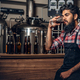 Indian male manufacturer tasting craft beer in the microbrewery. - PhotoDune Item for Sale