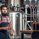 Indian male manufacturer presenting craft beer in the microbrewery. - PhotoDune Item for Sale