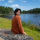 Back view of brunette lady in hat resting at lake in Karelia - PhotoDune Item for Sale