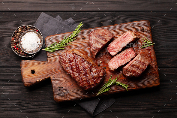 Grilled beef steaks on cutting board - Stock Photo - Images
