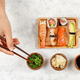 Top view of hand taking roll with chopsticks from a plate - PhotoDune Item for Sale