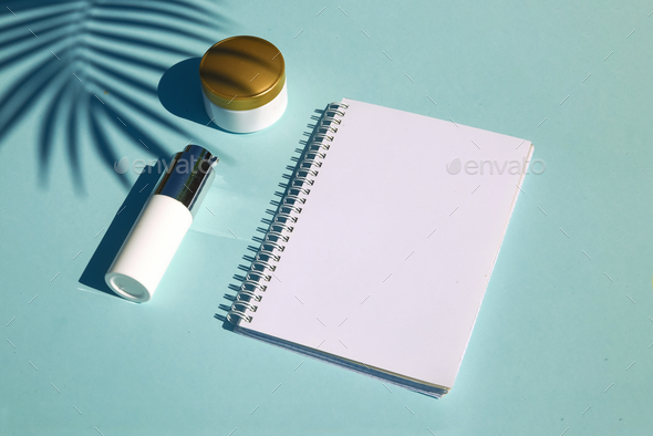 Cosmetic natural products on pastel blue background. Notebook for inscription - Stock Photo - Images