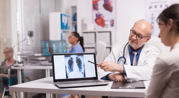 Senior doctor pointing at lungs x-ray - Stock Photo - Images