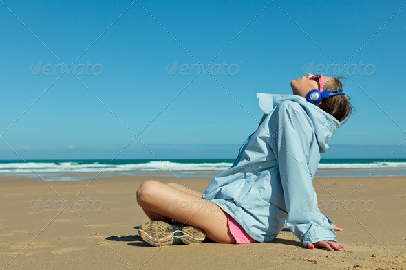 Fitness girl with headphones on the beach - Stock Photo - Images