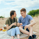 Young adult couple talking and having picnic on beach - PhotoDune Item for Sale
