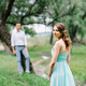 happy guy in a white shirt and a girl in a turquoise dress are walking in the forest park - PhotoDune Item for Sale