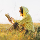 Young woman girl traveler in yellow hoodie reading book in sunrise - PhotoDune Item for Sale