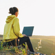 Young woman girl traveler freelancer in yellow hoodie with opened laptop outdoor - PhotoDune Item for Sale
