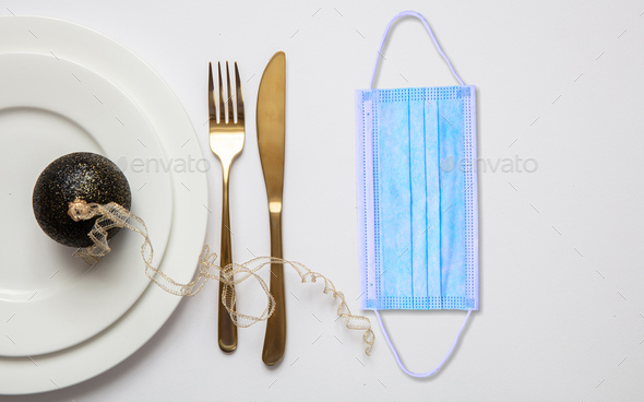 Coronavirus Covid19 christmas table concept, festive place setting with face mask - Stock Photo - Images