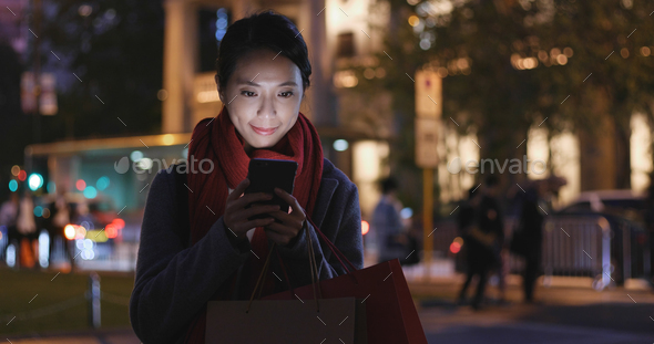 Woman use of smart phone in city at night - Stock Photo - Images