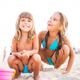 Two girls play on beach while sitting in sand - PhotoDune Item for Sale