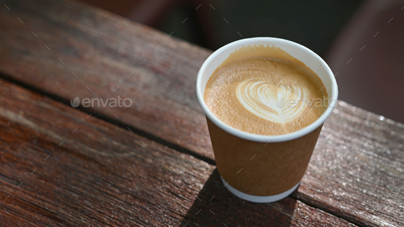 Close-up shot of Take away latte coffee mug placed on a wooden table. - Stock Photo - Images