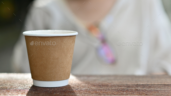 Close-up shot of Take away coffee mug placed on a wooden table. - Stock Photo - Images