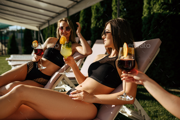 Women with coctails leisures on sunbeds, resort - Stock Photo - Images