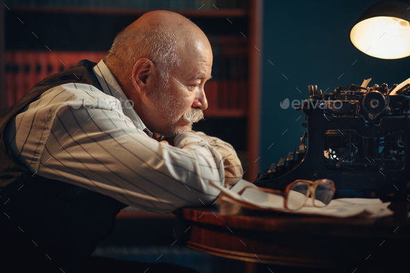 Elderly writer thinks at vintage typewriter - Stock Photo - Images