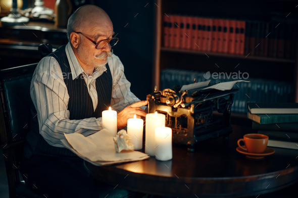 Adult writer works on typewriter with candle light - Stock Photo - Images