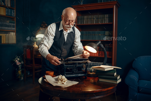 Elderly writer inserts paper into the typewriter - Stock Photo - Images