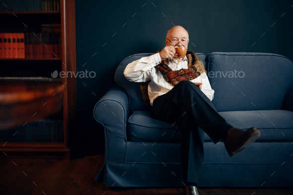 Elderly writer drinks coffee in home office - Stock Photo - Images