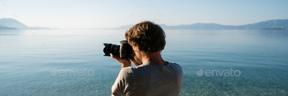 Young male photographer taking photos of beautiful summer landscape - Stock Photo - Images