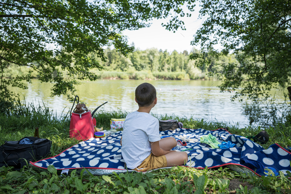 Boy sitting on picnic blanket by the lake - Stock Photo - Images