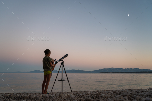 Brothers standing on beautiful pebble beach looking to the stars with a telescope - Stock Photo - Images