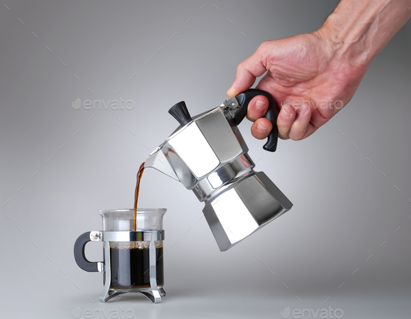 Man's hand holding and pouring italian coffee into a Glass cup - Stock Photo - Images
