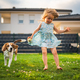 Baby girl running with beagle dog in garden on summer day. Domestic animal with children concept - PhotoDune Item for Sale