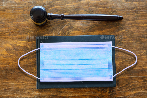 Protective mask and judge gavel on wooden office desk background, law - Stock Photo - Images