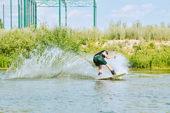 Back view of young active sportsman moving on surfboard and splashing water - Stock Photo - Images