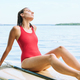 Young wet relaxed woman in swimsuit resting on surfboard and enjoying hot day - PhotoDune Item for Sale