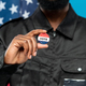Hand of bearded African male security in black uniform showing you vote insignia - PhotoDune Item for Sale