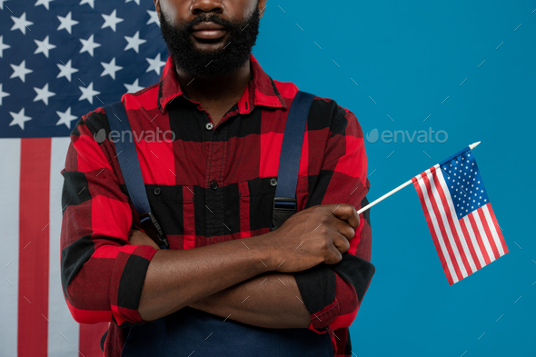 Young bearded repairman of African ethnicity in workwear holding American flag - Stock Photo - Images