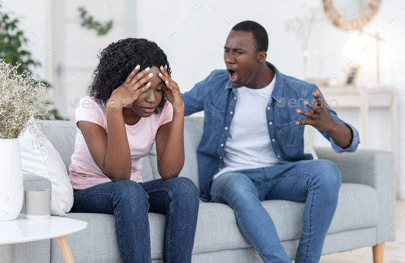 Angry black man yelling at his crying wife