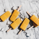 Flat-lay of homemade mango smoothie vegan popsicles over marble background - PhotoDune Item for Sale