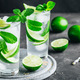 Mojito cocktail with ice, fresh mint and lime in glass on dark stone background. - PhotoDune Item for Sale