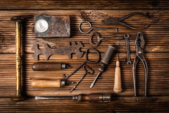 Collection of rusty tools and keys in vintage style on wooden background - Stock Photo - Images