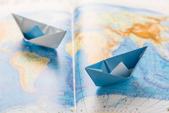 Paper boats on world map. Concept of traveling or military exercise. - Stock Photo - Images