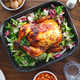 Decorated festive table with whole roasted chicken, salad, pumpkin, mushrooms, beans and walnut. - PhotoDune Item for Sale