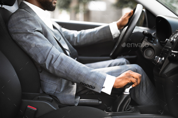 Closeup of black man in suit changing gears in car - Stock Photo - Images