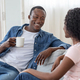 Lovely african couple drinking tea and having conversation - PhotoDune Item for Sale