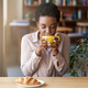 Pretty African American woman enjoying her morning coffee with croissant at urban cafe - PhotoDune Item for Sale