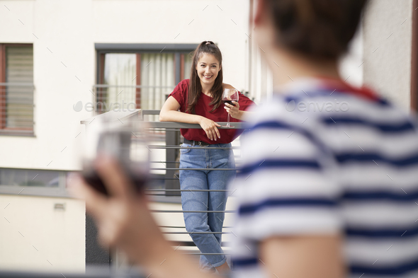 Women chatting while standing on their balconies - Stock Photo - Images