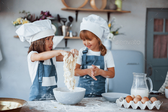 Family kids in white chef uniform preparing food on the kitchen - Stock Photo - Images