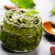 Glass jar with pesto sauce on stone table with basil leaves and garlic aside - PhotoDune Item for Sale
